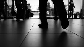 Accelerated black and white footage:people are leaving and coming to the airport stock video