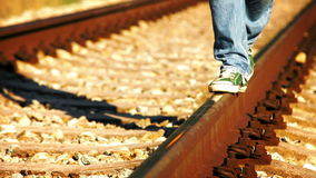 Accelerated footage of a teenager in jeans and sneakers walking along the rail stock footage