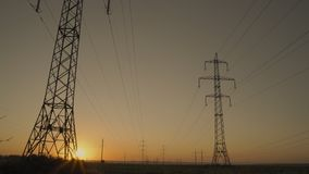 Accelerated Movement, the Sun Rises from beyond the Horizon and Shines Through the High Voltage Transmission Pedestal. At Dawn stock footage