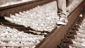 Accelerated sepia toned footage of a teenager walking along the rail wearing sneakers stock footage