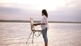 Accelerated shooting, a girl artist in the water till ankles draws a landscape using an easel and a palette. Curly girl stock footage
