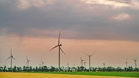 Accelerated video movement of clouds over wind power plants. Accelerated video movement of clouds over wind power plants in the middle of farmland. Time lapse stock video footage