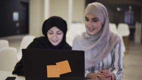 Accelerating footage of happy muslim businesswomen in hijab at office workplace or conference hall. Two smiling arabic stock video footage