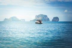 Acceleri la barca che galleggia sul mare con il fondo del cielo blu e dell'isola alla spiaggia di Railay Immagini Stock