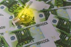 Accenda sui precedenti di euro soldi, l'elettricità costosa fotografia stock