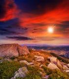 Accenda sul pendio di montagna di pietra con la foresta al tramonto Fotografie Stock Libere da Diritti