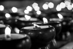 Accenda una candela nella sfuocatura scura Fotografie Stock Libere da Diritti