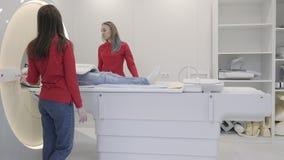 Accendere della donna l'analizzatore di RMI con il paziente maschio di menzogne stock footage