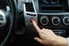 accendere il sistema di condizionamento d'aria dell'automobile, dito che colpisce il fondo della luce di emergenza dell'automobil Fotografie Stock Libere da Diritti