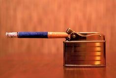 Accenditore e sigaretta del metallo Immagini Stock