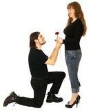 Acceptance. A man down on his knee giving his girlfriend a rose and the girl holding the rose. isolated on white Royalty Free Stock Images