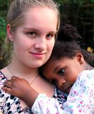 Acceptance. A teenage girl hold a young african american girl acceptance Stock Photography