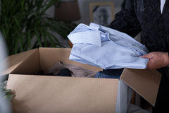 Acceptance of dead love. Woman putting her dead husband clothes into a box Stock Image