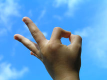 Acceptance gesture – child hand. Against clear blue sky with some fluffy clouds royalty free stock photos