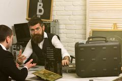 Accepting Bitcoin today will make your business ready for tomorrow. Businessmen in office with bitcoin symbol. Bearded. Men and customer negotiate a deal stock photography