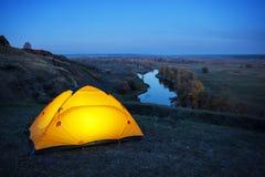 Acceso dentro la tenda arancio su una collina sopra il fiume fotografia stock
