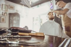 Accesories for cutting on the table in a barbershop. And a hairdresser works in the background. Photo in vintage style stock images