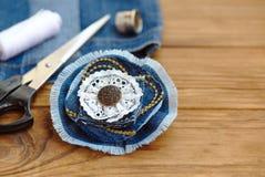 Accesorio de la flor del dril de algodón Tijeras, hilo, dedal, aguja, vaqueros viejos femeninos en una tabla de madera Idea recic Foto de archivo libre de regalías