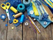 Accesorios amarillos y azules para la costura en fondo de madera El hacer punto, bordado, cosiendo Pequeña empresa Renta de la af Fotografía de archivo libre de regalías