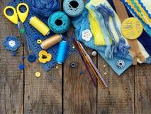 Accesorios amarillos y azules para la costura en fondo de madera El hacer punto, bordado, cosiendo Pequeña empresa Renta de la af Foto de archivo libre de regalías