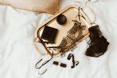 Accesorios atractivos para la mujer Artículos negros en la bandeja del oro Concepto del lujo del encanto Fotografía de archivo