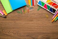 Accesorios brillantes de la escuela, efectos de escritorio en un fondo de madera, espacio de la copia, visión superior fotos de archivo