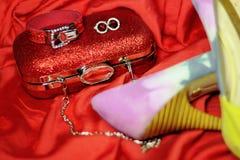 Accesorios brillantes hermosos y zapatos de tacón alto y un embrague rojo en el vestido de noche Foto de archivo libre de regalías