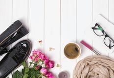 Accesorios, café y rosas del ` s de la mujer en la tabla de madera blanca Fotos de archivo