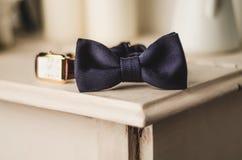 Accesorios clásicos del novio: corbata de lazo y reloj azules en una tabla de madera Sistema de la ropa vintage elegante de los h foto de archivo libre de regalías