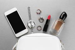 Accesorios, cosméticos, perfume y teléfono cerca de pequeño Imagen de archivo