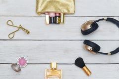 Accesorios, cosméticos rosa y colores oro femeninos en un w de madera Fotos de archivo libres de regalías