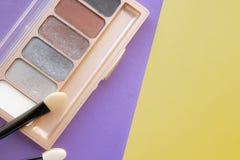 Accesorios cosméticos Un cepillo, sombreador de ojos en un amarillo, fondo púrpura foto de archivo libre de regalías