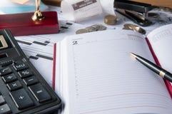 Accesorios cuaderno del negocio, calculadora, pluma y gráficos, tablas, cartas en un escritorio de oficina de madera Imagen de archivo libre de regalías