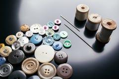 Accesorios de costura: botones, hilos y agujas en un fondo oscuro Imágenes de archivo libres de regalías