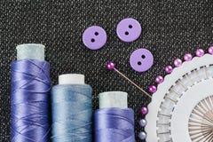 Accesorios de costura: carretes de los hilos, agujas, botones, en Imágenes de archivo libres de regalías