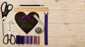 Accesorios de costura del color y del corazón púrpuras con una inscripción Imagen de archivo