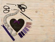 Accesorios de costura del color y del corazón púrpuras con una inscripción Fotos de archivo