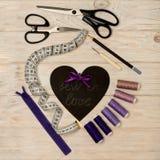 Accesorios de costura del color y del corazón púrpuras con una inscripción Foto de archivo libre de regalías