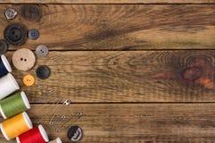 Accesorios de costura en fondo de madera Foto de archivo