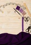 Accesorios de costura en un fondo de madera ligero de la púrpura y del li Foto de archivo libre de regalías