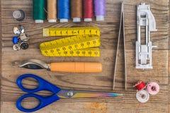 Accesorios de costura: hilos coloreados, dedal, pinzas de costura, pie de costura, bobinas, tijeras, cinta de la medida, botones Fotos de archivo libres de regalías