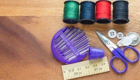 Accesorios de costura púrpuras en la tabla interior de madera Imagenes de archivo