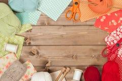 Accesorios de costura y que hacen punto Tela, bolas del hilado Tabl de madera Imágenes de archivo libres de regalías