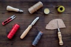 Accesorios de cuero del arte Herramientas y matherials en la opinión superior del fondo de madera oscuro Fotos de archivo libres de regalías