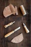 Accesorios de cuero del arte Herramientas y matherials en la opinión superior del fondo de madera oscuro Imágenes de archivo libres de regalías