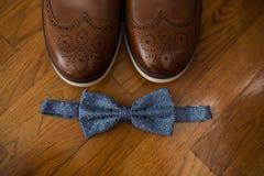 Accesorios de Groom's: corbata azul y zapatos de cuero marrones en un fondo de madera Foto de archivo