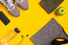 Accesorios de la aptitud en un fondo amarillo Las zapatillas de deporte, la botella de agua, la manzana y el deporte rematan imagen de archivo