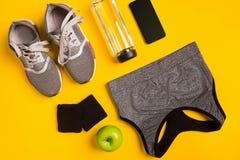Accesorios de la aptitud en un fondo amarillo Zapatillas de deporte, botella de top del agua, elegante y del deporte imagen de archivo