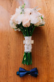 Accesorios de la boda: corbata de lazo del novio, ramo nupcial de las rosas blancas en la tabla de madera Fotos de archivo