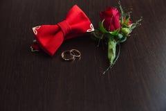 Accesorios de la boda del novio Boutonniere, anillos de oro y corbata de lazo rojos en fondo marrón Foto de archivo libre de regalías